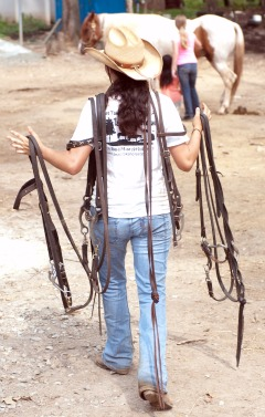 Girl Carrying Horse Bridles